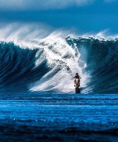 Robbie Maddison, on a motorcycle with paddle tires, rides a wave in Tahiti.