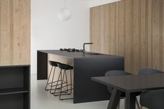 The kitchen features custom cabinetry and a large sliding door, both made from oak, that provides recessed storage space. The black theme continues with the furniture, including HAY About A Stool (AAS 38) models around the kitchen island and the HAY About A Chair (AAC 22) set.