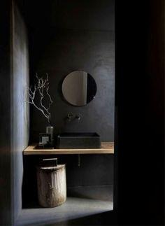 Schwarze Wände, eine schwarze Wanne und ein hölzerner Kostenzähler und Hocker, die Beschaffenheit hinzufügen