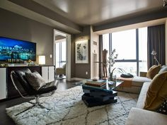 The selection of low-profile furnishings was purposeful in this modern living room: when one walks into the apartment, views through floor-to-ceiling windows remain unobstructed.