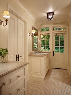 Fantastic master bathroom his his and her vanities composed of cream cabinets with nickel hardware and stone countertops. Cream cabinets with beveled countertops paired with beveled mirrors flanked by nickel sconces. Master bathroom features French doors with oil-rubbed bronze door knobs leading to bathing room and basketweave tile floor.