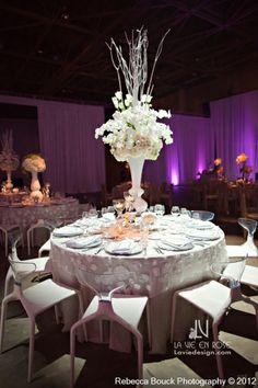 Skyscraper centerpiece with white French Tulips, Phalaenopsis Orchids, Ranunculus, Roses, and Hydrangea.