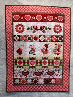 """""""Be Mine, Valentine""""  2013 Quiltmakers Quilt Guild Row by Row project.  Completed 12-11-13.  The pattern was actually a Christmas design and larger in size.  Modified to a Valentine's Day theme and reduced to 60% of the original. Because the quilt blocks were so small I drafted paper piecing patterns for them.  The piecing and quilting were done by machine, all applique and embroidery embellishment was hand work."""