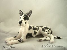 """CDHM Artisan Malinik Miniatures, www.cdhm.org/user/malinik. Titled: Harlequin Great Dane - Miniature Custom Dog - gift for pet lovers. Described as, """"The Great Dane is handmade from polymer clay and wire armature for the legs, painted with acrylic paints and sealed. Then for the coat I applied white fiber flocking, marking with acrylics and fabric pen."""" 1:12 Dollhouse miniature dog."""