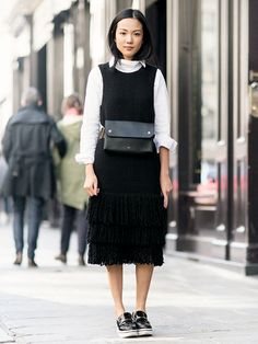 Black dress worn over a white button up, belted at the waist with a fanny pack