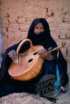 Africa | Tuareg woman playing an Imzad. Traditional instrument consisting of a goatskin covered gourd or wooden resonator played with a curved bow and horsehair string. Niger | ©Eye Ubiquitous