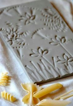 25 Cute Clay Art Tutorials for Kids - Hobby LessonClay Tiles using Pasta as Texture for sensory-rich art explorations (via Arte a Scuola)A simple and brilliant idea to be realized at school with clay slabs: colored tiles imprinted with different shapes of Clay Tiles, Ceramic Clay, Clay Plates, Kids Clay, Clay Projects For Kids, Clay Crafts For Kids, Toddler Crafts, Cute Clay, Paperclay