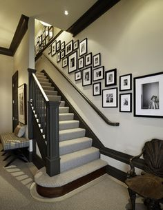 Dragons Breath by Benjamin Moore on trim. Nicely balanced arrangement of frames up the stairs. #gallery wall #foyer