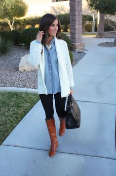 Stay stylish on busy days in a white knit open cardigan and black leggings. Tobacco leather knee high boots will bring a classic aesthetic to the ensemble.  Shop this look for $112:  http://lookastic.com/women/looks/knee-high-boots-leggings-tote-bag-denim-shirt-open-cardigan-pearl-necklace/6840  — Tobacco Leather Knee High Boots  — Black Leggings  — Black Leather Tote Bag  — Light Blue Denim Shirt  — White Knit Open Cardigan  — White Pearl Necklace