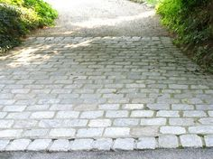 Cobblestone entry. This is a great way to dress up a driveway. It's costly, but think about doing the rest of the driveway loose stone, asphalt, or tar and chip. Much nicer and less expensive than an all paver driveway in my opinion! Loose stone will need an edging but steel edging is not that expensive.
