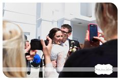 Reasons to Have an Unplugged Wedding: Not smiling faces, but cameras surround the couple.