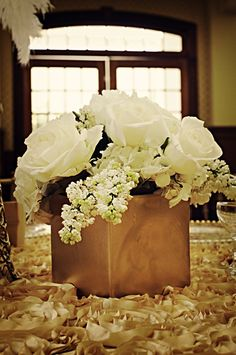 Low centerpiece... featuring white/ivory roses, white/ivory hydrangea, white/ivory pieris japonica (wedding bells) - just add a few ivory pearls popping out with a single shimmering gold plume feather... I believe this is very close to Tina's vision