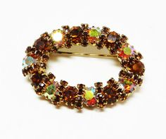Vintage Oval Brooch - Brown & Yellow Aurora Borealis Rhinestones - 1960s - 1970s Pin - Vintage Rhinestone Jewelry offered by TheJewelSeeker on Etsy  Description & Style: This is a sparkling and lovely oval brooch with a donut hole style opening in the center. The open centered brooch is made with yellow aurora borealis and brown rhinestones. The classic style is from the 1960s - 1970s. Its beautiful vintage rhinestone jeewelry from an era where jewelry was made well and worn daily!  Color…