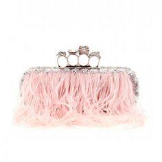 CLUTCH EMPOLVADO: de color rosa candy con aplicaciones de plumas, punch metálico y charms en forma de calavera. Es de Alexander McQueen.