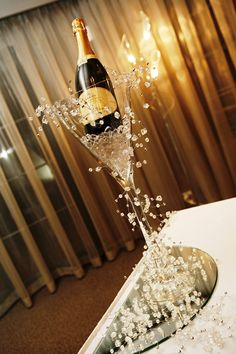 Large Martini vase with ice and Champagne with silver garland, looks like Champagne popping.
