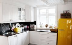 Neutral Norwegian kitchen with pops of yellow — including a yellow SMEG refridgerator!