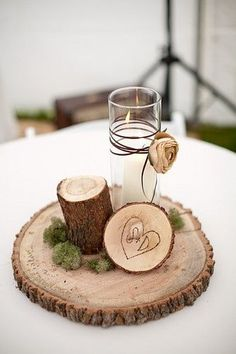rustic - enchanted forest wedding reception table centerpieces -- log slices, carved initials, moss, candle, twine with dried flowers.