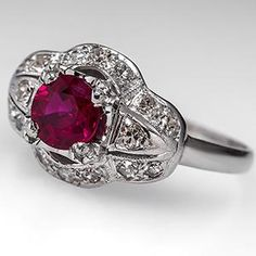 This lovely vintage ruby engagement ring is centered with a gorgeous .56 carat ruby in an openwork setting. The ruby is lightly included and grades a fabulous vivid red in color. The ring is accented with bead set single cut diamonds set into the modified navette shaped head and finished with milgrain edging. This ring is crafted of solid platinum and is in good condition with a fresh polish.
