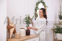 Woman decorating home interior with eucalyptus branches. Buy Creativity & Imagination. Take a look at what the world's best photographers have to offer at africa-images.com Eucalyptus Branches, Best Photographers, Photo Library, Ladder Decor, Africa, White Dress, Stock Photos, Creative, Interior