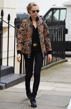 Cara Delevingne adds edge to an all-black look with a Chanel belt, floral bomber, and sunnies.