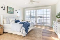 white upholstered bed with blue bedding in a lake house master bedroom Rustic Master Bedroom, Bedding Master Bedroom, Master Bedroom Design, Bedroom Decor, Bedroom Ideas, Master Suite, Bedroom Designs, Bedroom Furniture, Royal Bedroom