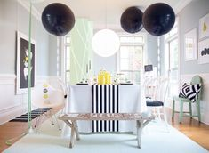 Mod Cow Party: mint paper table runners hung from ceiling at staggered intervals // giant black balloons anchored with white cow bells