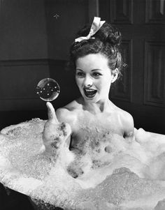 Jeanne Crain balances a soap bubble on her index finger as she luxuriates in a bath in a scene from the 1946 movie, Margie.