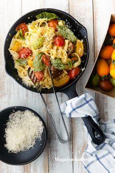 Przepis na szybki makaron z pomidorami. Makaron przesmażony na patelni z oliwą, kolorowymi pomidorami, posypany bazylią i świeżo startym parmezanem.
