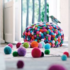 Poufs and carpets handmade of woolen pompoms. Colorful decor idea for the home.
