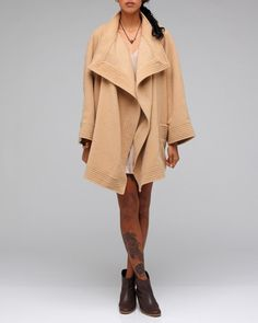 Oversized, vintage inspired camel coat with open collar styling with stripe seaming detail, large front bucket pockets, drop shoulder fit, and kimono style sleeves from Kristinit. Fully lined.    100% Organic Wool