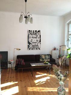 Lichtdurchflutetes Wohnzimmer Mit Dunkler Couch Und Kunstdruck In Berliner 3 Zimmerwohnung Zwischenmiete