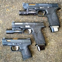 """For any M&P fans out there with the 3 variants, WE m&p with custom slide kits, Top one is based on the M&P9 pro with a salient slide kit from prime/nova, ready fighter magwell, ace 1 arms sai trigger, 5"""" pdi 6.01 barrel and maple leaf hop rubber, and detonator vtac sights, replica x300u. Middle one based on M&P9 with a detonator Atei costa ludus slide kit, ready fighter magwell, ace 1 arms sai trigger, detonator vtac sights, 4.25"""" maple leaf 6.02 barrel and hop rubber, replica x300u. Bott... Smith Wesson, Smith And Wesson Shield, Tactical Gear, Tactical Pistol, M&p Shield, Firearms, Handgun, Custom Guns, Revolver"""
