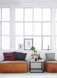 leather poufs & framed pictures/prints artfully leaning, rather than hanging..chic!