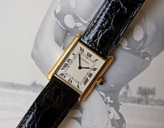 Men's Cartier Tank Louis Cartier in solid 18k Yellow Gold with stunning silver guilloché Roman numeral dial.  Features the very slim Cartier caliber 021, which is based on the Frederic Piguet cal. 21P.  On a picture of the lovely Bettie Page.