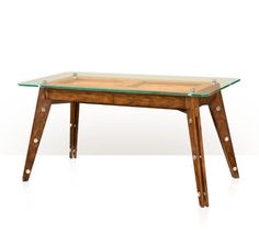 A Hyedua crown veneered writing table, the floating rectangular glass top with canted corners above two frieze drawers, on splayed angular tapering legs with stainless steel rivet decoration.