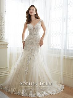 Sophia Tolli - Y11643 – Daria - Fiesta tulle over point d'esprit fit and flare wedding gown with slight lace cap sleeves, tip-of-the-shoulder plunging V-neckline with modesty panel, hand-beaded lace appliqué bodice with beaded midriff trim and dropped waist, semi sheer back bodice with keyhole and back corset, appliqués cascade down skirt, scalloped hem lace, chapel length train. Also available with a back zipper as style Y11643ZB.Sizes: 0 – 28Colors: Almond, Ivory, White