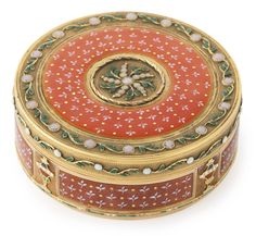 A gold and enamel circular box, Swiss or German, circa 1785 enameled on all sides with trefoils on salmon ground within foliage borders with opalescent beads, the sides with champlevé urns at intervals, in a fitted case marked inside cover and base with pseudo marks