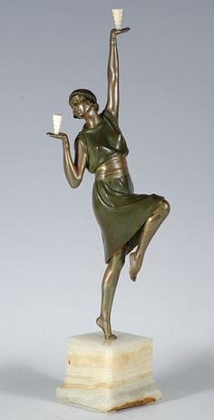 Balancing Act, a cold painted bronze figure of a young lady balancing two ivory prisms whilst dancing, by Demetre Chiparus (1888 - 1947). Raised on a cream onyx plinth    Signed    H 43cm    French, circa 1925