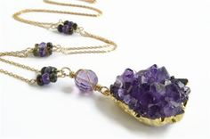 Purple Amethyst Druzy Cluster pendant dangles from a beautifully faceted wire wrapped amethyst.  Faceted amethyst and tourmaline natural gemstones enhance the chain. Deep purple amethysts and tourmaline in shades of dark greens and browns add rich color.  Chain measures approximately 28 inches and has a spring ring closure.  All necklace metals are 14 Kt Yellow Gold Filled.  The edges of the amethyst cluster pendant are plated with a thick layer of gold. The back of the stone has been…