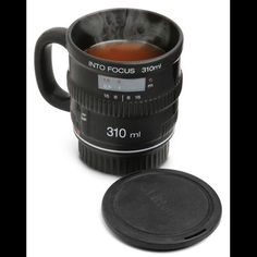 Sure you've seen coffee mugs shaped like camera lenses before, but where those failed, this picks up. First, it's made of ceramic, not plastic. Second, there's a handle. You're not likely to accidentally pour a freshly brewed pot of Ethiopian Sidamo into your prized 24mm to 105mm f2.5 zoom lens if you're expecting a handle through which you loop your index finger.   $16.50  http://www.graygoose.com/collections/all/products/into-focus-camera-lens-mug