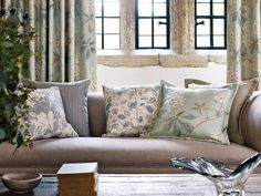 A selection of cushions made from fabric found in the Sanderson SS16 collection 'Woodland Walk' featuring beautifully drawn chestnut tree leaves, creeping woodland berries and painterly magnolia flowers