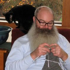 He looks very relaxed knitting with his cat nearby.