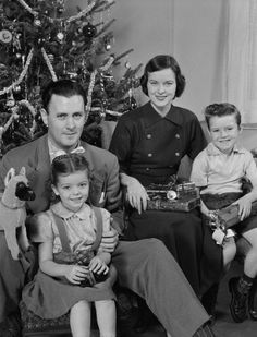1950s Family portrait by christmas tree.