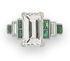 An art deco diamond and emerald ring, circa 1925  The rectangular step-cut diamond, weighing 4.92 carats, claw-set between tiered shoulders set with baguette-cut diamond and rectangular-cut emerald accents sold for £16,800