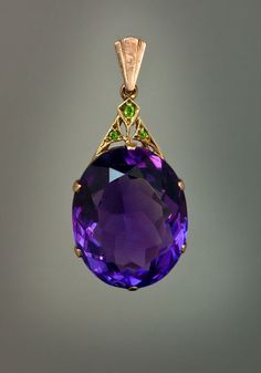 An Art Deco Siberian Amethyst, Demantoid Garnet and Rose Gold Pendant Necklace - The pendant features an oval cut large Siberian amethyst with an approximate weight of 30.5 carats.  The Art Deco gold mount is set with three Uralian demantoids.  Moscow, circa 1930 Height with bail - 40 mm (1 9/16 in.)  Sold.  RomanovRussia.com