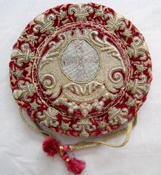 ♪ 17th century gaming bottom. This is a special purse for use at the gaming table, to hold money or counters. Its style is quite different from other 17th-century purses. The flat, circular base with sides gathered on a drawstring prevented spilling or revealing the contents, and the coat of arms on the bottom identified the owner.