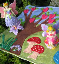 Mini Play Scene Pouch - Fairy Cottage. This quilted fabric mini play mat opens out to a magical woodland scene. Inside a cute cottage pocket you will find a 3 little plastic fairies who just love to come out and play among the heart tree, toadstools, flowers and pool.... The Old Button Play Mat designs are copyrighted
