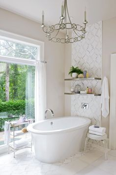 A beige-and-white bathroom is ideal when pairing with a backyard view. An expansive window lets color in year-round, so the neutral beige paint color is perfect for matching each season's shades. #bathroomideas #bathroomcolorschemes #beigebathrooms #bathroomdecor #remodel #bhg