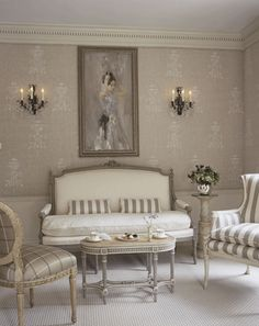 """In soft impressionistic strokes, the painting above a settee and two chairs in the room's gathering area introduce the only note of color--a delicate lilac--in an otherwise tightly composed symphony of ivory and gray."" Traditional Home Magazine, showhouse bathed in white. Oh, we  agree."