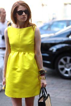 Vestido amarelo e várias pulseiras.